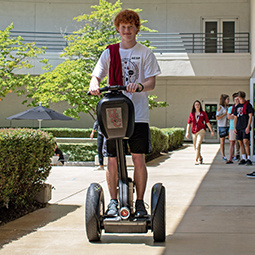 male student rides a segway in the courtyard