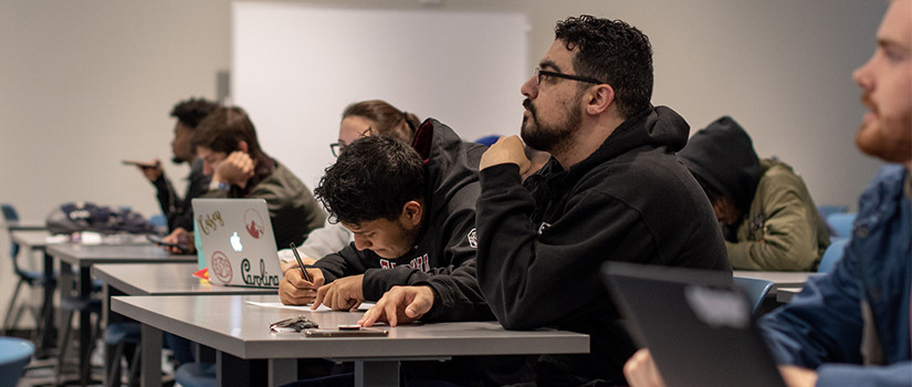 row of students take notes in class