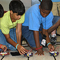 two students prepare to race robotic cars