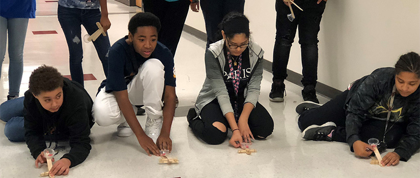 students test out popsicle stick creations in the hallway