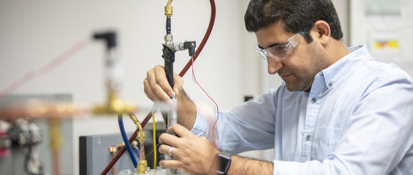 man works with electrical equipment in a lab