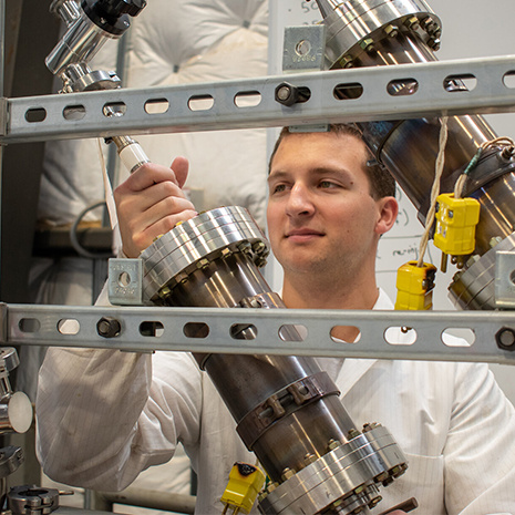 a grad student works with nuclear fuel rods