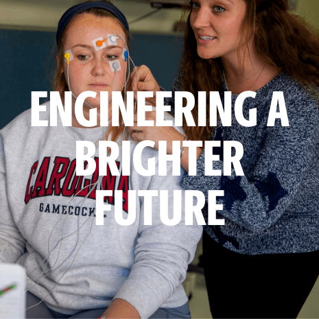 Engineering a brighter future over a photo of two female students working with electrodes in a lab