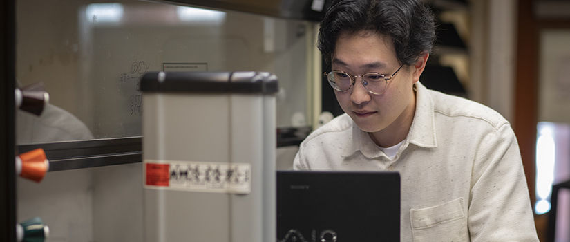 grad student looks at laptop in the lab