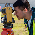 student looks through surveying equipment