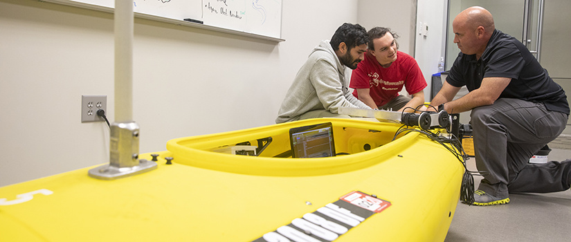 students and professor kneel next to robotic kayak