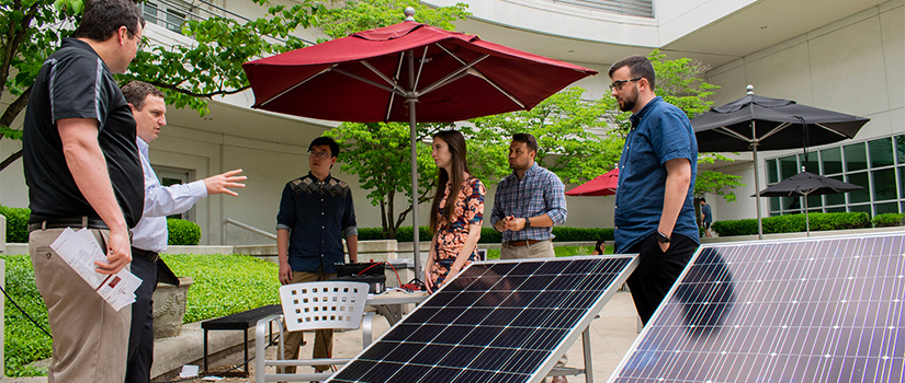 students work with solar panels in the courtyard
