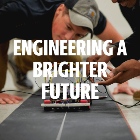 text: engineering a brighter future over a small electric car and two male students