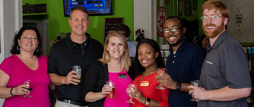 Young Alumni Board Members stand with Dr. Gazke at Craft and Draft