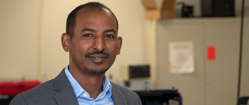 Addis Kidane stands in his lab.