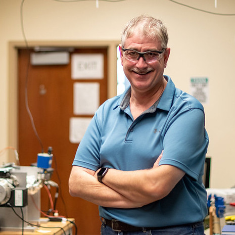 Dr. Lauterbach stands in his lab wearing saftey glasses