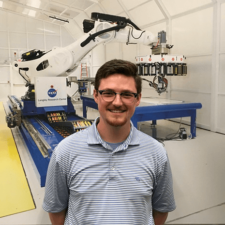 Jackson Swiney poses in front of a machine at NASA