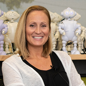 Laura Boccanfuso in front of shelf of small white robots