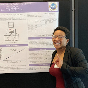 a Black woman stands by her research poster