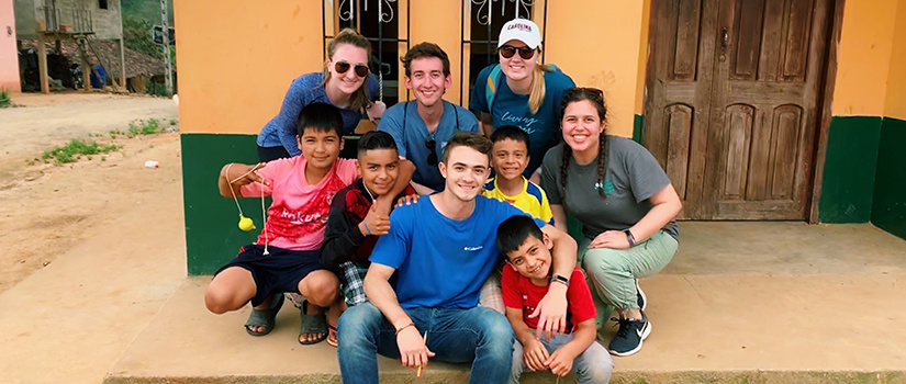 group of UofSC students poses with children in Ecuador