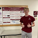 Jonathan Gray stands next to a research poster