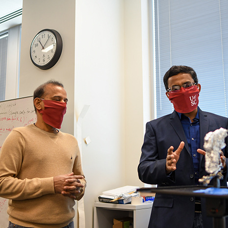 two professors talking wearing masks