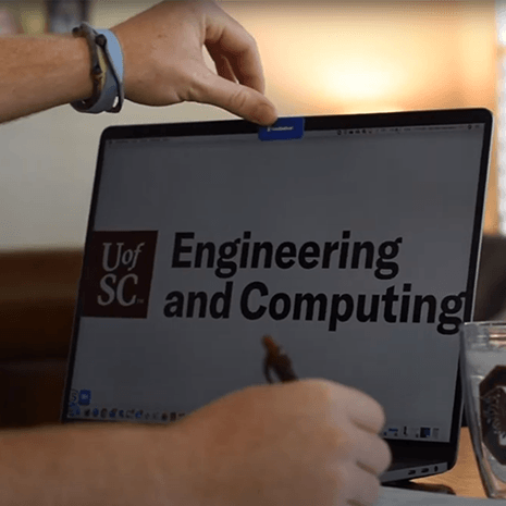 hand opening a computer with the college logo