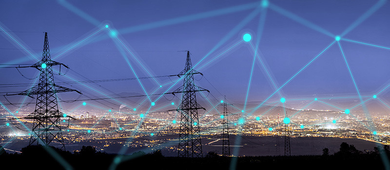 Stock photo of power lines heading toward a city.