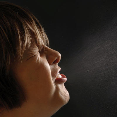 woman sneezing with visible droplets