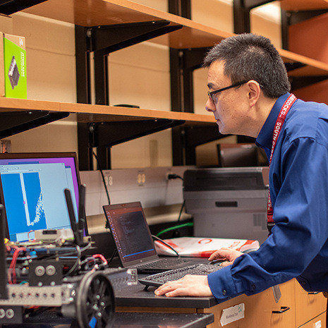Dr. Wang works on a laptop in his lab