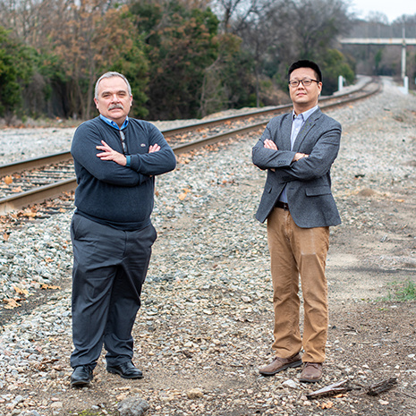 Dr. Rizos and Dr. Qian in front of railroad tracks