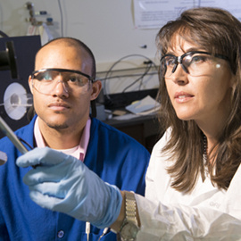 two researchers look at a screen