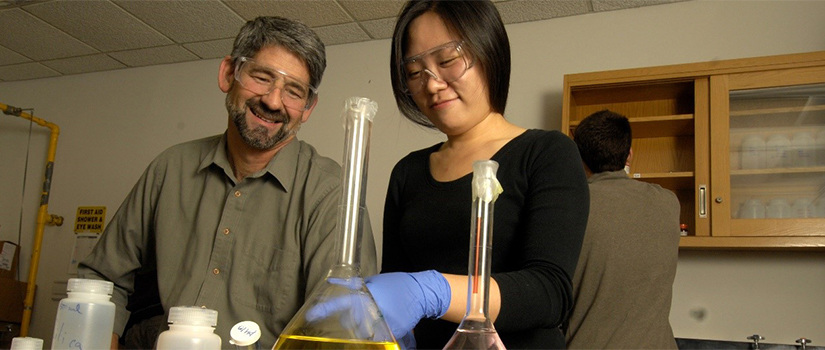 Dr. Regalbuto works with a female student in a lab