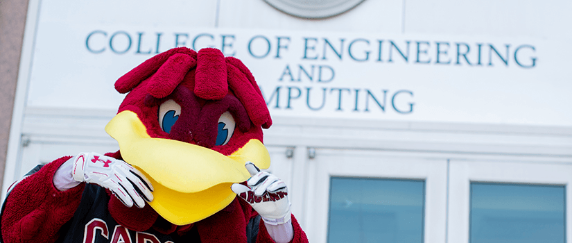 cocky poses in front of the engineering building