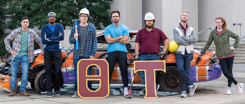 seven theta tau students wear hard hats and pose at the annual Clemson Car Smash