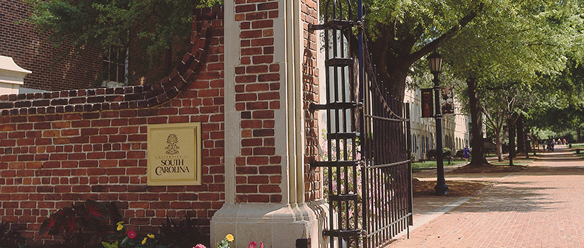 Large brick wall and column with a gold University of South Carolina plaque and the gate open in welcome to the historic Horseshoe area of campus, looking down the brick sidewalk to green space and students walking in the distance..