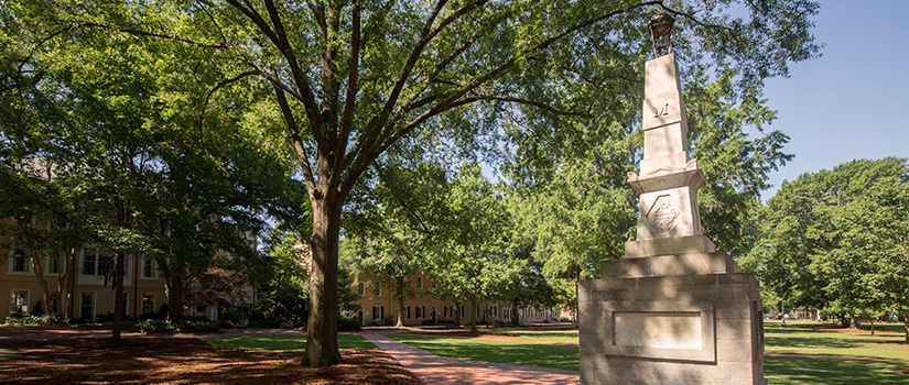 The Maxcy Monument in the historic Horseshoe area of campus, dappled with sun shining through the tree next to it.