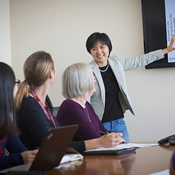 A female Asian presenter disucsses material on a projector with three other women one of whom is wearing an official UofSC lanyard and one of whom is also of Asian descent.