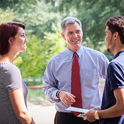 Two students one male and one female talking to a male professor outside with greenery in the background.