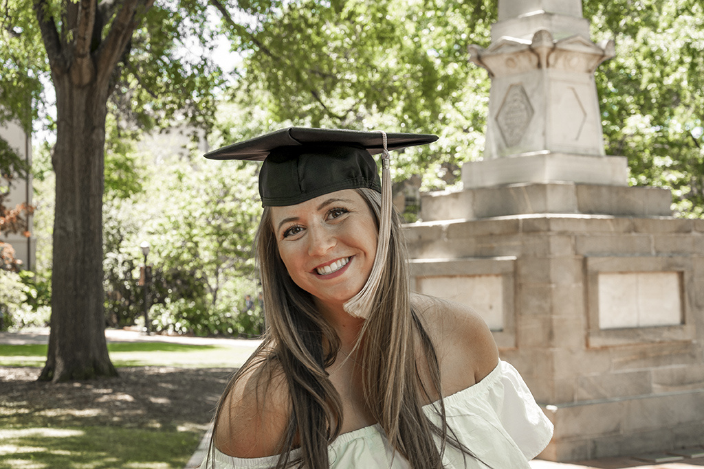 Madelyn Anderson models our graduation cap on the Horseshoe.