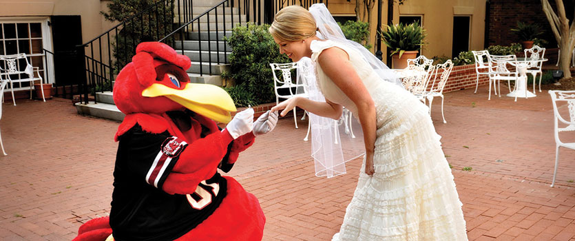 "Cocky ""proposes"" to a blushing bride on the patio of the historic McCutchen House."