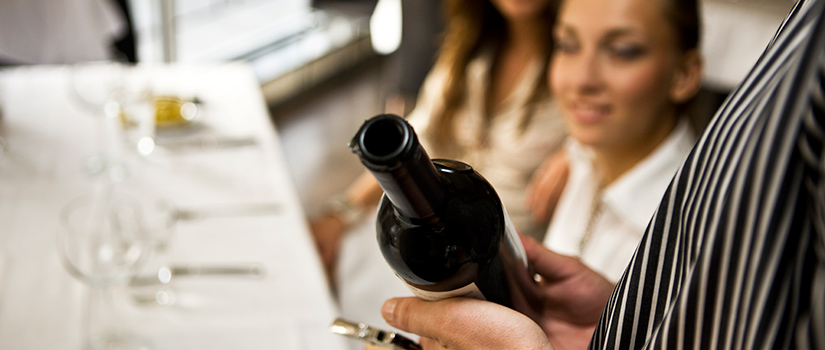 An instructor describes a bottle of wine to a class of onlookers.