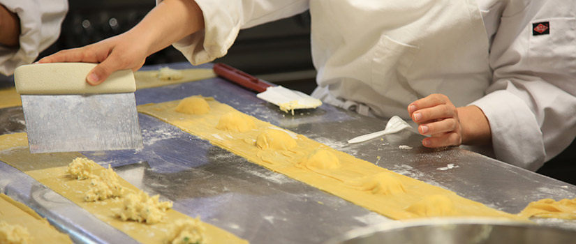 A culinary student learns how to make fresh pasta and from that create ravioli. Here her hands are shown cutting the pasta to ravioli size.