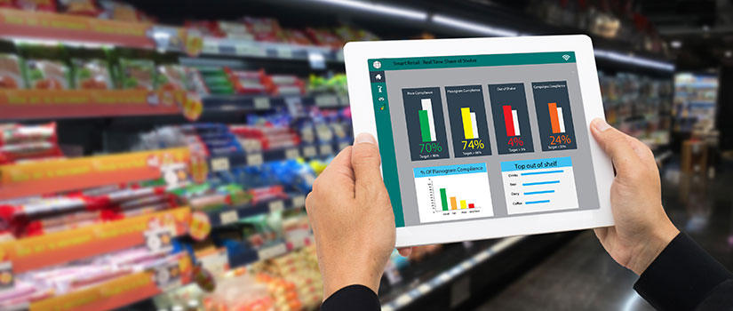 A category management analyst views statistics on a mobile pad in a grocery store.