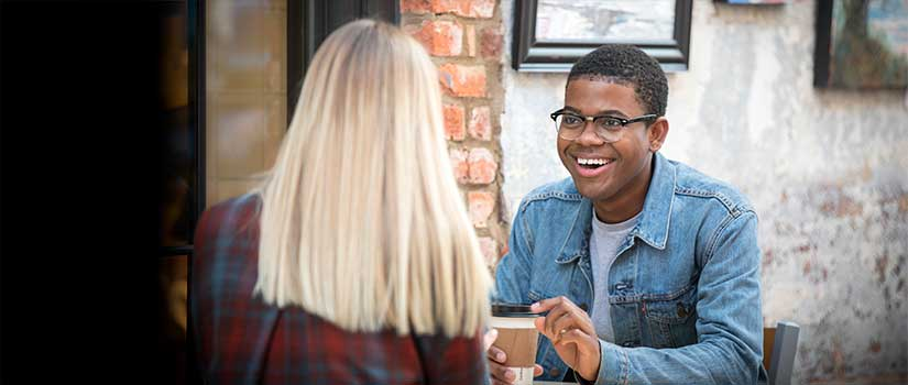Dashon Murray sits outside at a sidewalk coffee shop sharing a laugh with another student.