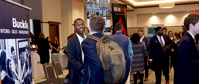A recruiter from Buckle speaks with an HRSM student at the 2020 College of HRSM Experience Expo.