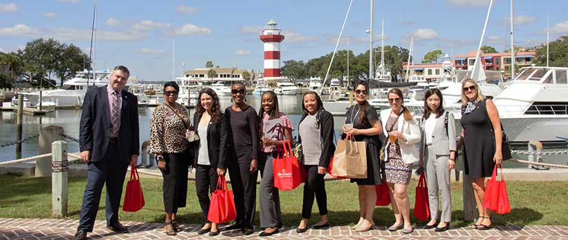 International students pose in Hilton Head's Harbor Town boat basin, a key tourist area for Sea Pines Resort visitors.