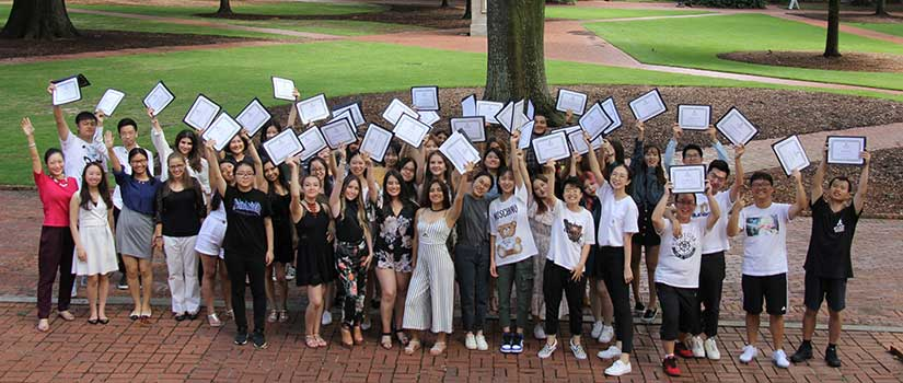 Photo of international students with their certificates held high on the lush green space known as the Horseshoe at the historic heart of the University of South Carolina