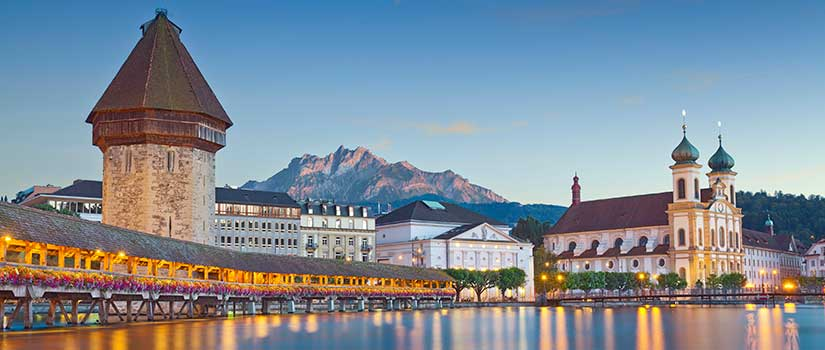 The Lucerne Campus in Switzerland sits on the banks of Lake Lucerne amidst snowy mountain peaks and lush landscape.