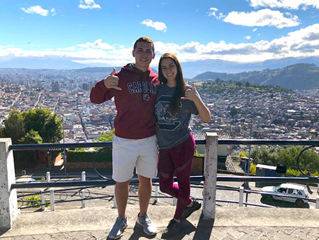 "Two HRTM students pose ""spurs up!"" at an overlook in Quito, Ecuador. The students were able to visit the city while spending a semester studying in the Galapagos."