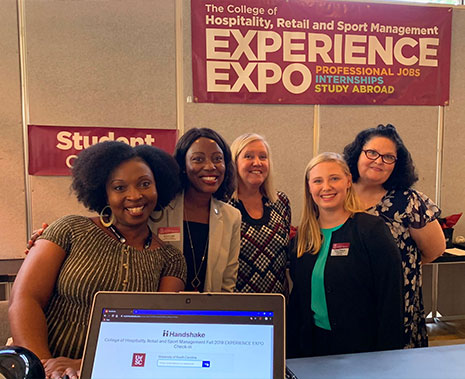 Erica Lake stands with student volunteers at the 2019 Experience Expo.