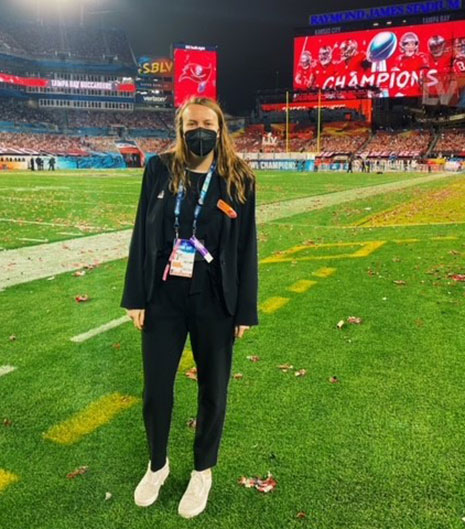 Logan Hudson stands on the field at Raymond James Stadium preparing for Super Bowl LV