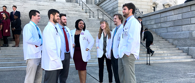Students in white coats on the State House steps