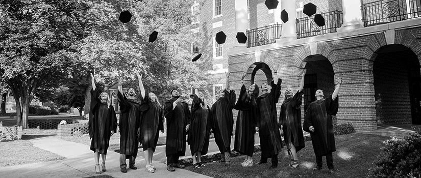 Students in graduation robes tossing caps