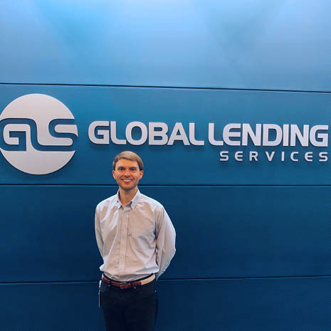 Matt Pangle standing infront of company logo